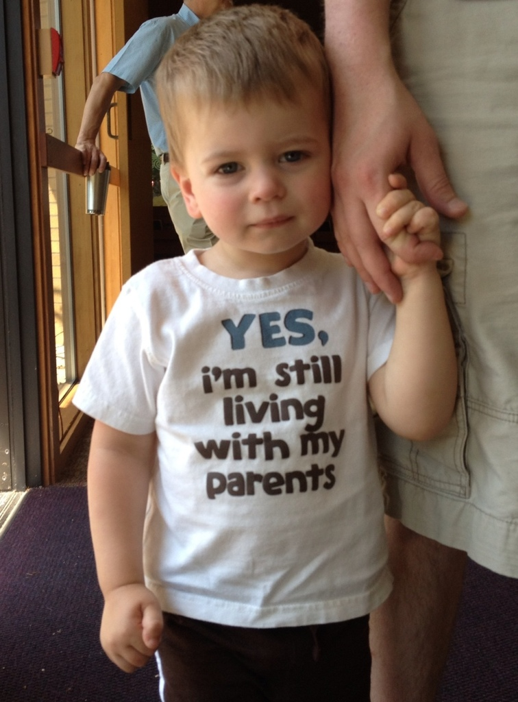 young boy wearing a shirt that says Yes, I'm still leaving with my parents
